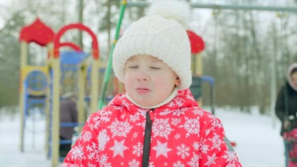 Smutný chlapeček na hřišti v zimě