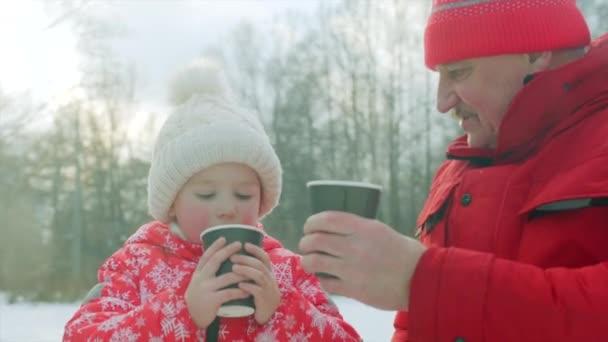 Kleiner Junge und sein Großvater trinken heißen Tee nach dem Schlittschuhlaufen auf dem See