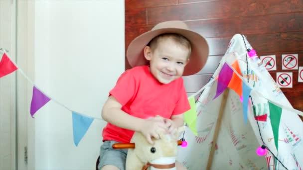 Boldog kisfiú, cowboy kalapot visel a lovaglás egy játék a játszószobában