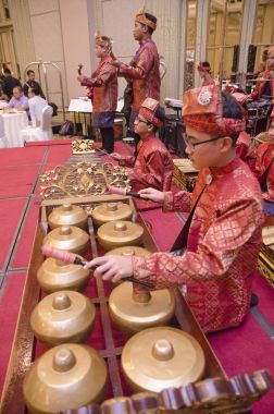 KUALA LUMPUR, MALAYSIA 12 JULY 2017: Group of Malaysian with songket performing Gamelan Orchestra and modern music instrument