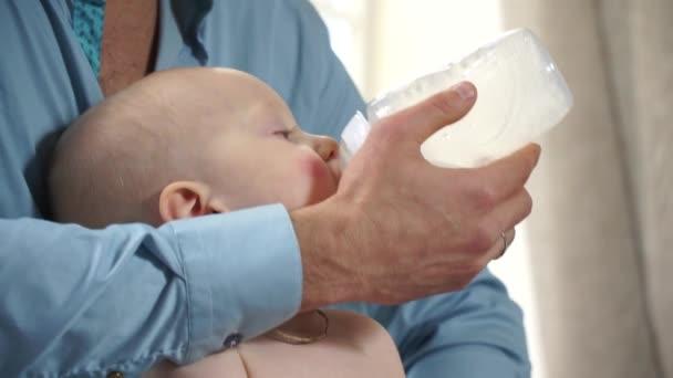 Closeup dad feeding baby