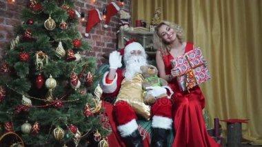 Šťastná dívka v dlouhé červené šaty sedí vedle Santa s dárky