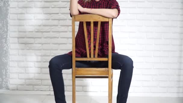 Sexy girl is sitting on a chair adjusting his glasses