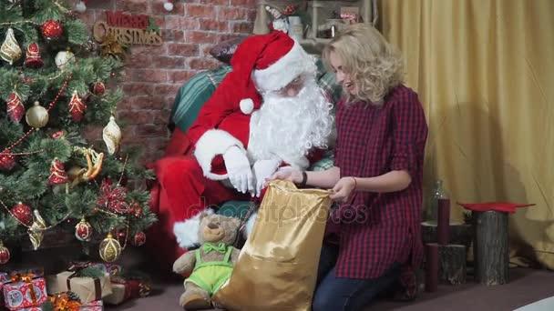 Santa a dívka zírá do pytle s dárky