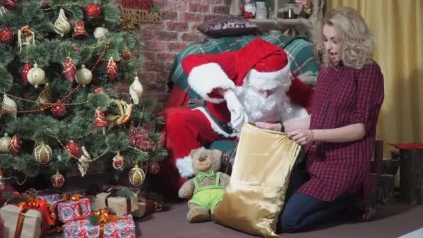 Veselý Santa vypadá v sáčku s dárky překvapení dívka