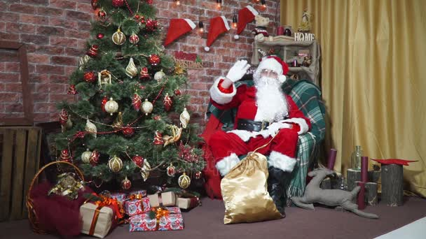 Santa winkt seine Hand beim Sitzen auf einem Stuhl am Weihnachtsbaum