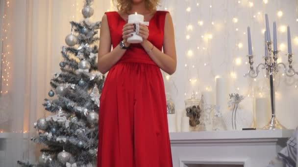 Dívka v dlouhé červené šaty s velkými rty a svůdné oči foukání svíčky