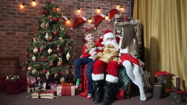 Mädchen nimmt die Tasche vom Weihnachtsmann mit Geschenken und Teddybär