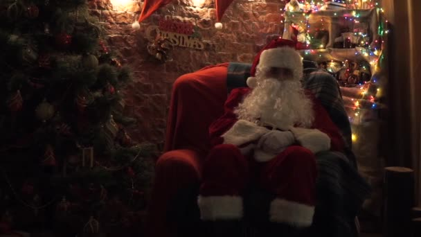 Santa Claus sedí v křesle u vánočního stromu