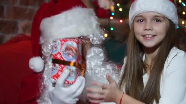 Closeup dívka dostane dárek od Santa Claus