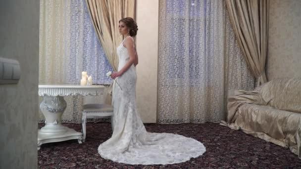 ddcf414c1f1 Schlanke Braut in einem wunderschönen Brautkleid mit langer Schleppe–  Stock-Filmmaterial