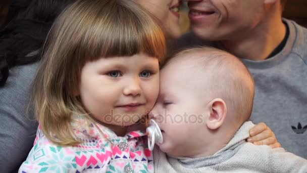 Close-up of small children and parents kissing