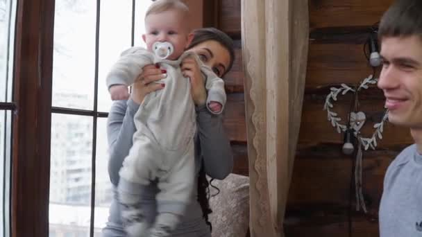 Mom playing with baby son. Dad takes daughter in his arms