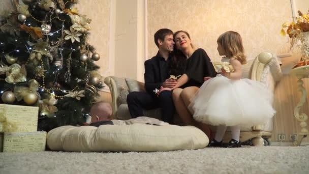 Glückliche Eltern mit kleinen Kindern in der Nähe von the Christmas tree
