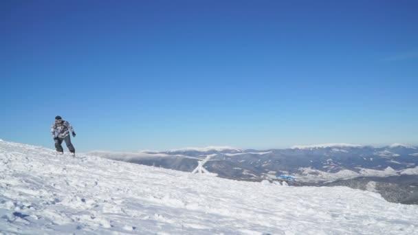 Snowboardista sestupuje na zasněžený svah
