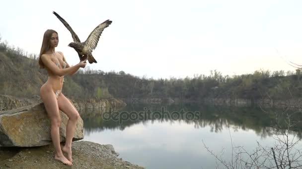 Nahá dívka s ptákem v blízkosti jezera v lomu