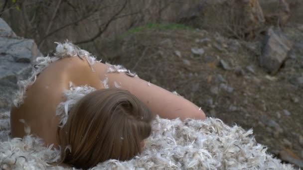 Dívka spí na peří uprostřed lesa