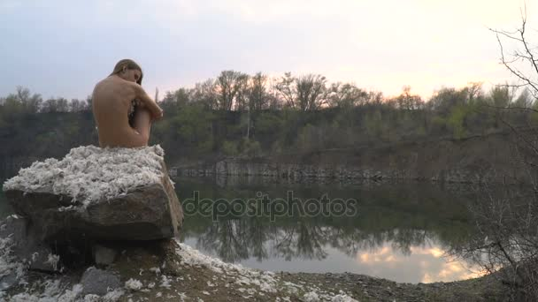 A lonely girl sits on a rock by the lake among feathers