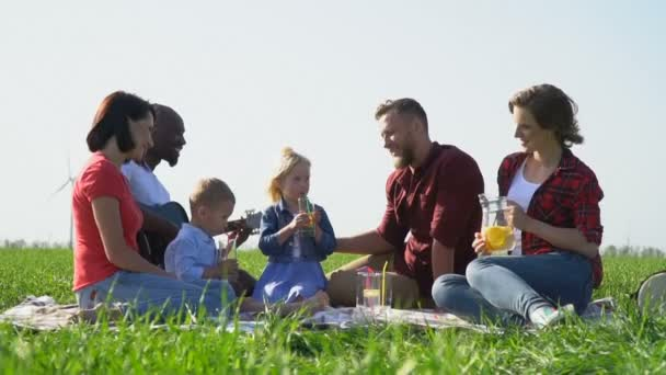 People with children rest on a picnic and drink fruit water