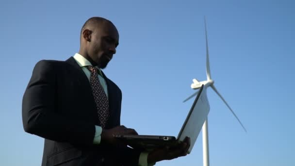 Pensive black man in a business suit with a laptop in hand near a wind generator, slow motion