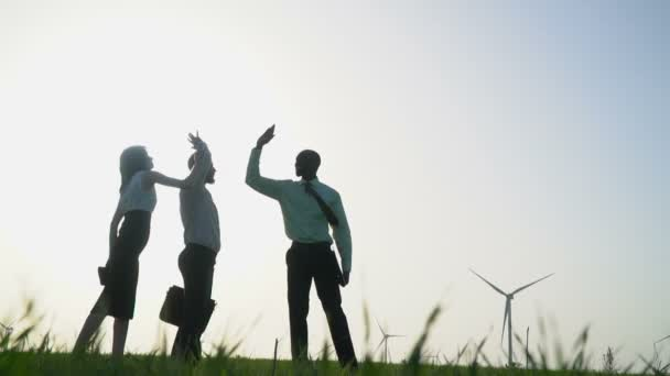 A group of people in business suits gives high five at wind generators background, slow motion