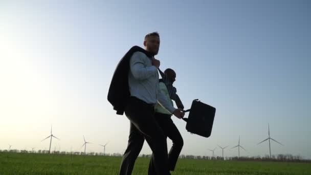 Men in business suits are walking along a green meadow near the wind generators and one of them is throwing out a briefcase