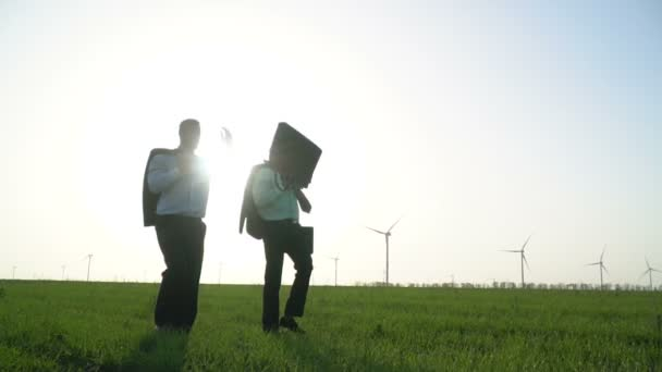 Men in business suits are walking along a green meadow near the wind generators and one of them is throwing out a briefcase, slow motion