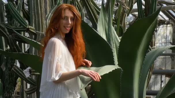 Redhead with flowing hair in white dress shows tongue