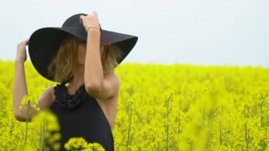 Charming girl in black among the field of canola
