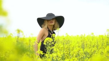 The girl walks among the bright field of canola
