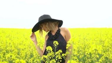 Girl in black posing amongst field of canola, slow motion