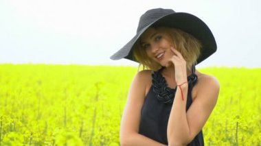 A cute girl in black posing in the middle of a field of canola