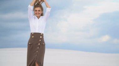 45ea7ec1e0a040 Een gelukkig meisje staat in het midden van de woestijn tegen een  achtergrond van donkere wolken