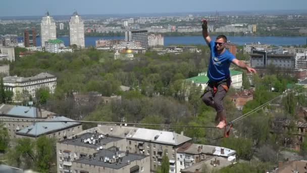 A man in a blue T-shirt gently stands up and walks on tight rope