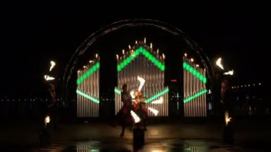 A beautiful dance with fire sticks on the night fire in front of a burning organ