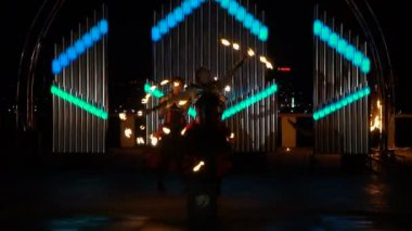 An unusual dance with fire fans on the fire show