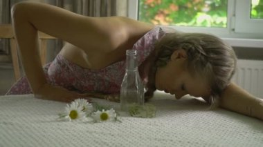 The woman is lying on the table among the daisies