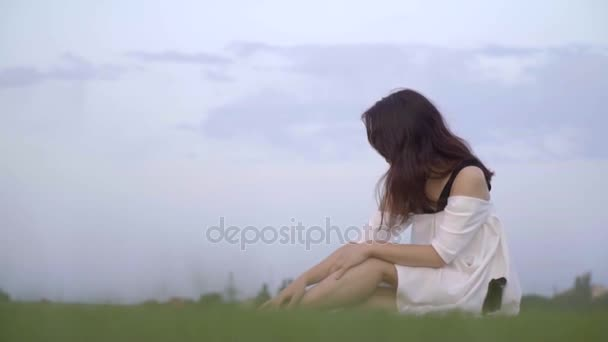 Japonská dívka v bílých šatech s úsměvem vypadá opět sedí na trávníku, pomalý pohyb