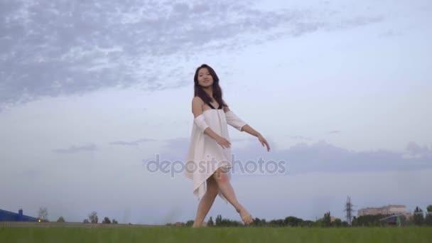 Danseuse étoile Japonaise Mince Dans Une Robe Blanche Sur La Pelouse Ralenti