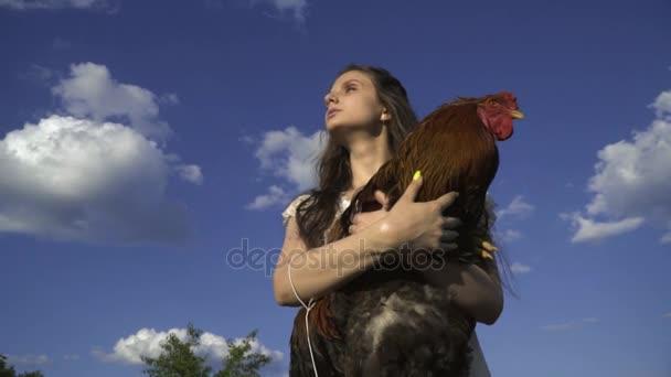 Bruneta s kohoutem v rukou na pozadí mraků, život na venkově