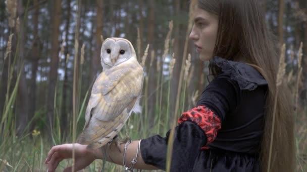 Krásná sova s světle peří v černé lesklé oči vypadá za sama, sedět na rukou pěkná dívka uprostřed lesa