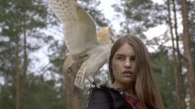 A light brown owl sits on the girls shoulder and climbs on her head clinging to her hair, which surprises the girl