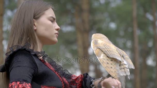 Světle hnědá sova pomalu šíří křídly sedící na ruku dívky uprostřed lesa