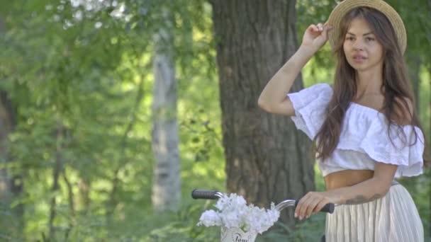 Pěkná brunetka v bílých šatech a klobouk je stát se město kolo uprostřed parku a čeká na někoho, Zpomalený pohyb, Střelba