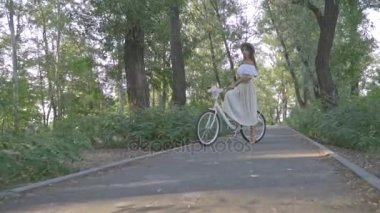 A kamera roll egy karcsú barna-fehér szoknya, blúz és nádfedeles hat, hogy a city Bike park közepén áll, és elküldi a légi csók