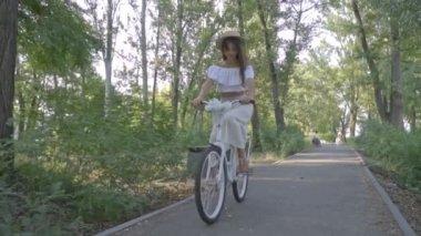 Barna-fehér szoknya, blúz és egy szalmakalapot túrák a város kerékpáros az úton, a parkban, lassú mozgás, lövés