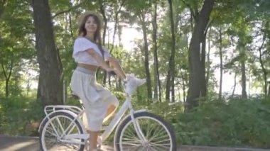 Szép barna-fehér szoknya, a blúz túrák a város kerékpáros az úton, a parkban és leveszi a Szalmakalapot és majdnem leesik a kerékpár, lassú mozgás, lövés