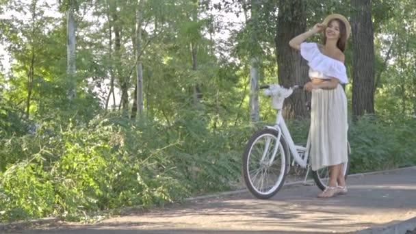 Krásná bunette v bílých šatech a čepice stojí s městské kolo na geek v parku a usmívající se čeká na někoho