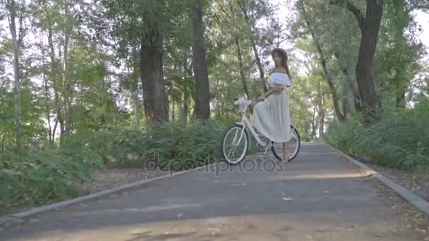 Fotoaparátu na štíhlá brunetka v bílé sukni, blůzu a doškové klobouk, který stojí uprostřed parku s městské kolo a posílá polibek vzduchu