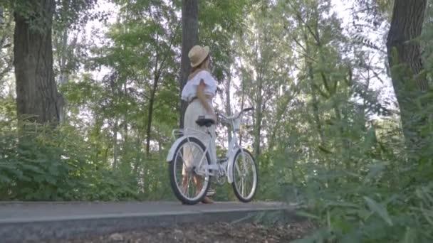 Fotoaparát chytá na štíhlounkou dívku v bílé sukni, blůzu a slaměný klobouk, který stojí uprostřed parku s městské kolo a hledá někoho, mezi lidmi, zpět zobrazení. Zpomalený pohyb